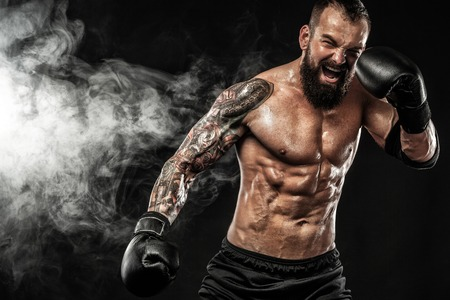 Sportsman muay thai boxer fighting on black background with smoke. Copy Space. Sport concept. Stock fotó