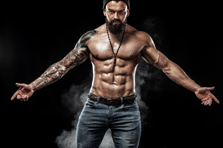 Handsome fit man posing wearing in jeans with tattoo. Sport and fashion concept isolated on black background. Standard-Bild