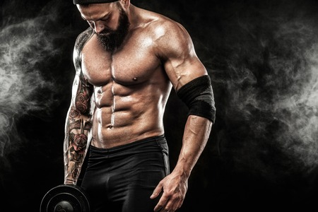 Muskularny mężczyzna młody fitness sport trening z hantlami w siłowni fitness