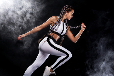 A strong athletic, woman sprinter, running on black background wearing in the sportswear, fitness and sport motivation. Runner concept with copy space. Фото со стока