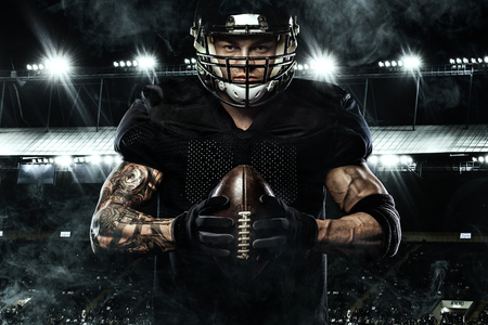 Sport concept. American football sportsman player holding ball on stadium.
