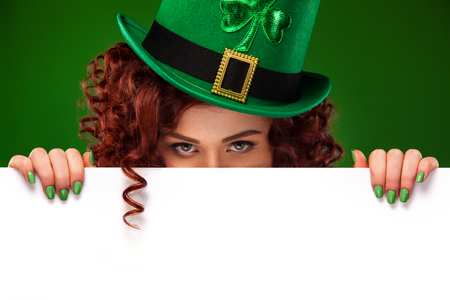 St patricks day. Young sexy ginger Oktober fest woman leprechaun, wearing a traditional Bavarian dress, serving big beer mugs on green background with banner for copy space