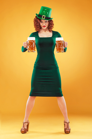 Saint Patricks Day. Young ginger Oktoberfest leprechaun, wearing grenn dress and hat, serving big beer mugs on orange background.. Banco de Imagens