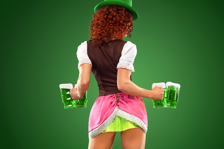 St Patricks Day. Young sexy Oktober fest waitress, wearing a traditional Bavarian dress, serving big beer mugs on green background with copy space