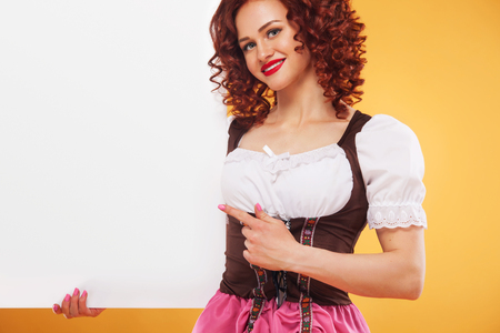 Happy smiling woman in pin-up style dress, showing blank signboard with copyspace, isolated over white background. Redhead model posing on yellow background with banner.