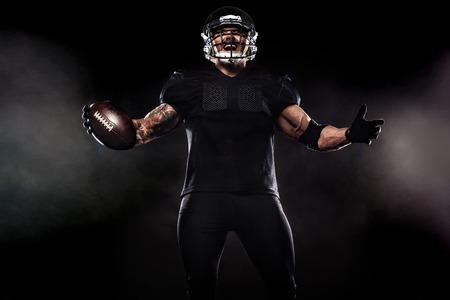 De Amerikaanse speler van de voetbalsportman die op zwarte achtergrond wordt geïsoleerd