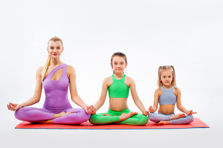 Hatha yoga fitness . Young mother Instructor and daughters exercise gymnastic together. Isolated on white background. Family look.
