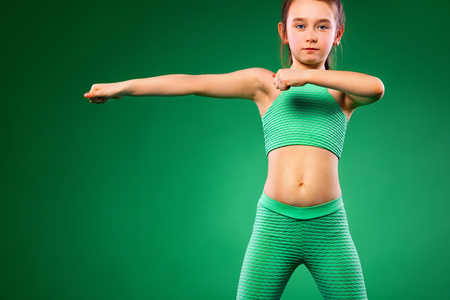 Kid girl doing fitness exercises on green background Stockfoto