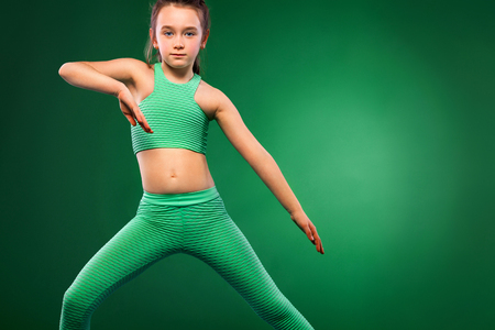 Kid girl doing fitness exercises on green background 免版税图像