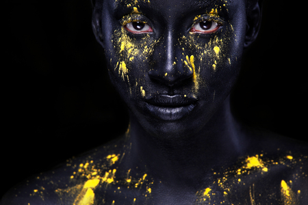 Cheerful young african woman with art fashion makeup. An amazing woman with black makeup and leaking yellow paint