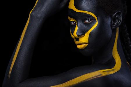 Alegre joven africana con maquillaje de moda de arte. Una mujer increíble con maquillaje de pintura negra y amarilla. Foto de archivo