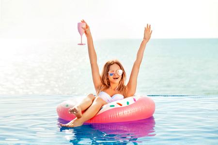 暑假。穿着比基尼的女人在水疗游泳池的充气甜甜圈床垫上。
