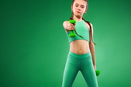 Kid girl doing fitness exercises with dumbbells on green background
