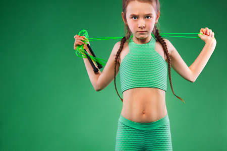 Kid girl doing fitness exercises on green background Standard-Bild - 101660420