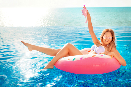 Summer Vacation. Woman in bikini on the inflatable donut mattress in the SPA swimming pool. Travel to the sea rest concept.