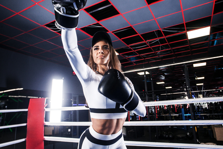Young athlete woman in boxing gloves standing on ring Stock Photo