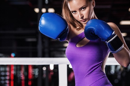 Portrait of a confident young athlete woman posing in boxing gloves standing on ring