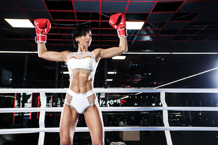 Young athlete woman in boxing gloves standing on ring Imagens