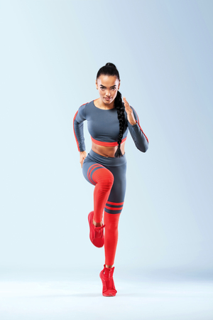 A strong athletic, women sprinter, running wearing in the sportswear, fitness and sport motivation. Runner concept with copy space. Dynamic movement Stock Photo