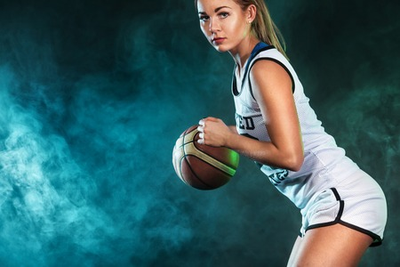 Portrait of a beautiful and sexy girl with a basketball in studio. Sport concept