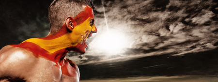 Soccer or football fan on stadium with bodyart on face - flag of Spain.
