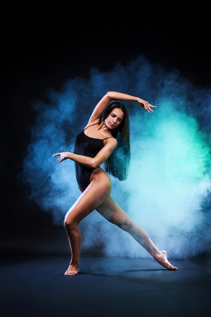 Beautiful young and fit ballet dancer jumping on a black background. Dance and sport concept.
