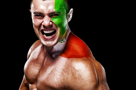 Soccer or football fan with bodyart on face with agression - flag of Spain.