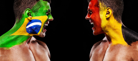 Soccer or football fan with bodyart on face with agression - flags of Brazil vs Belgium. Sport Concept with copyspace. Banco de Imagens