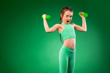 Kid girl doing fitness exercises on green background Stok Fotoğraf