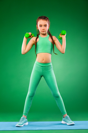 Kid doing fitness exercises at home in her room