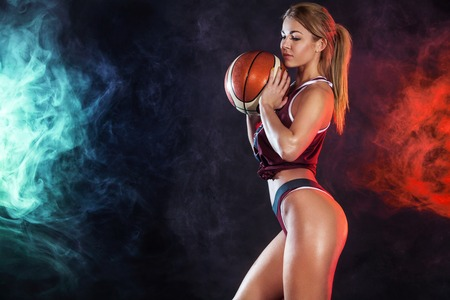 Beautiful and fit woman with a basketball in studio. Sport concept