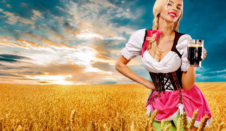 Half-length portrait of young sexy blonde with big breast wearing color dirndl with white blouse holding the beer mug Isolated on blue background