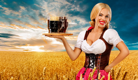 Half-length portrait of young sexy blonde with big breast wearing color dirndl with white blouse holding the beer mug Isolated on blue background Banque d'images - 106606642