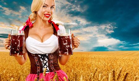 Halblanges Porträt einer jungen Blondine mit großem, farbigem Dirndl mit weißer Bluse, die den Bierkrug isoliert auf blauem Hintergrund hält