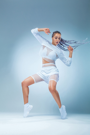 Attractive excited fitness girl dancer in sportwear dance isolated over blue background. Fashion and livestyle concept. 免版税图像 - 107087620