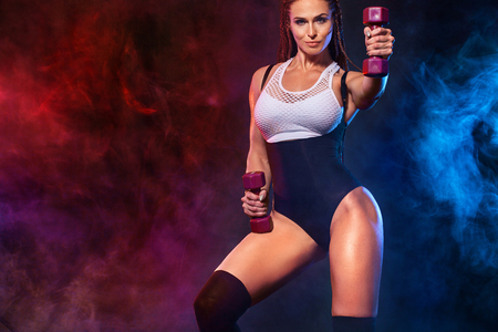 Attractive young fitness woman athlete and bodybuilder holding dumbell. Copy space for fitness nutrition ads.