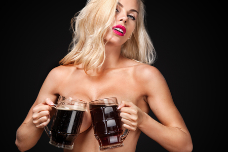 Oktoberfest Beer fest. Young sexy and naked woman, serving big mugs on dark background.