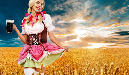Beer party. Sexy Oktoberfest woman - waitress, in Munich wearing a traditional german Bavarian dress, serving big beer mugs on golden wheat field background.