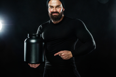 Happy and healthy muscular young fitness sports man with a jar of sports nutrition - protein, gainer and casein Stock Photo