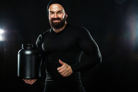 Happy and healthy muscular young fitness sports man with a jar of sports nutrition - protein, gainer and casein Stock fotó
