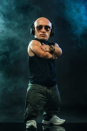 Portrait of stylish midget MC in with headphones and sunglasses posing with microphone. Stock Photo
