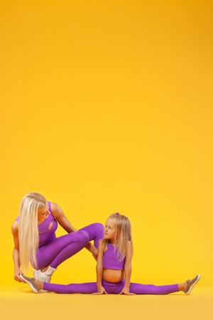 Hatha yoga fitness . Young mother and daughter exercise together indoors. Family look. Stock Photo