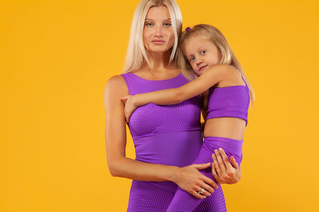Mothers day concept. Fitness family look. Young mother athlete and daughter exercise together indoors.