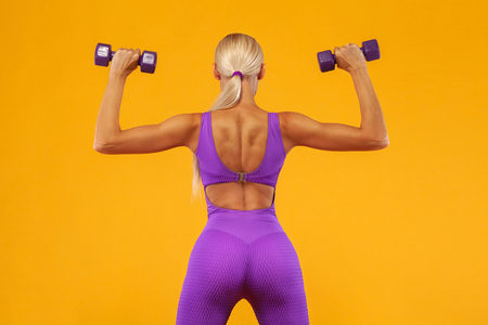Fitness woman athlete and bodybuilder holding dumbbell . Isolated on yellow background. Фото со стока - 109481923