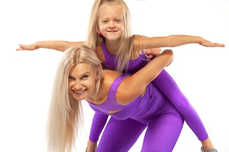 Mothers day concept. Young mother and daughter exercise fitness together indoors. Family look. Stock Photo