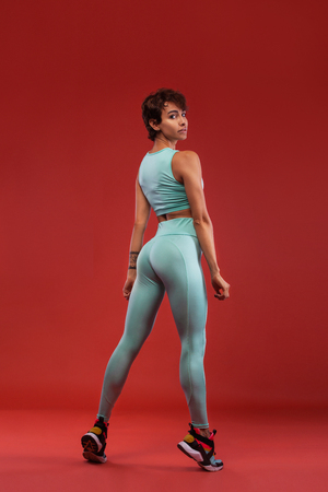 A Strong athletic, female runner on the black bacground wearing a tight, fitness outfit. Stock Photo