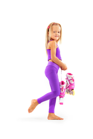 Girl, kid posing in studio wearing inline rollerskates