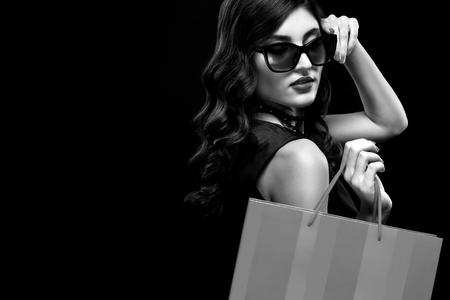 Christmas or Black friday sale concept. Shopping woman holding bag on dark background in holiday. BW photo.