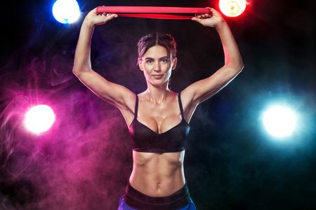 Fit sports woman athlete. Workout with bands or expander in gym with colorful bright blue and red lights. Imagens