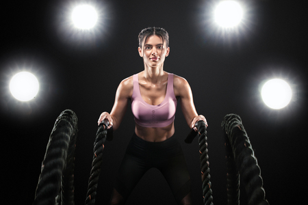 Battle ropes. Fit sports woman, athlete working out in functional training doing exercise on black background. Fitness, gym and workout motivation. Stock Photo